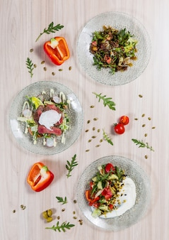 Three salads in glass plates on light wooden table in a restaurant. ingredients on the tab