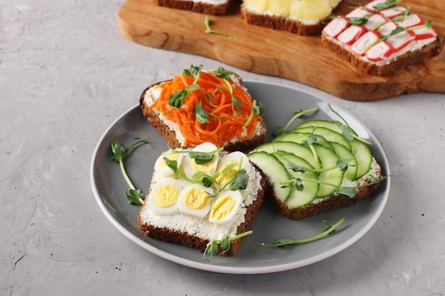 Три бутерброда на тосте со сливочным сыром, морковью, огурцом и перепелиными яйцами, украшенные горошком микрозелень, на тарелке на сером бетонном фоне, горизонтальный формат