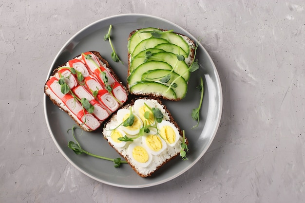 Three sandwiches on toast with cream cheese, cucumbers, quail eggs and crab sticks decorated with microgreens peas