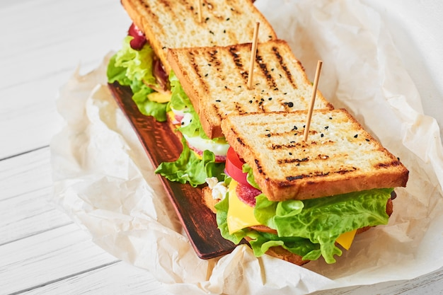 Three sandwiches with ham, lettuce and fresh vegetables on a plate, close up