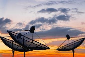 Three satellite dish black or TV antennas on twilight sky background.
