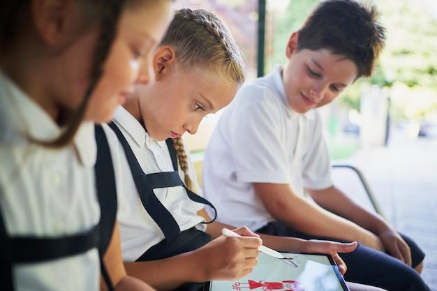 Трое школьников сидят в банке и рисуют на планшете