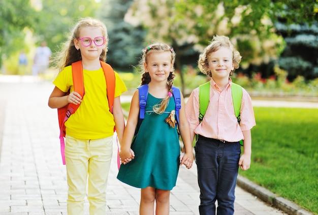 Трое школьников - две девочки и кудрявый мальчик с разноцветными школьными сумками, улыбаясь, держатся за руки и идут в школу. снова в школу концепции, 1 сентября, день знаний, образование.