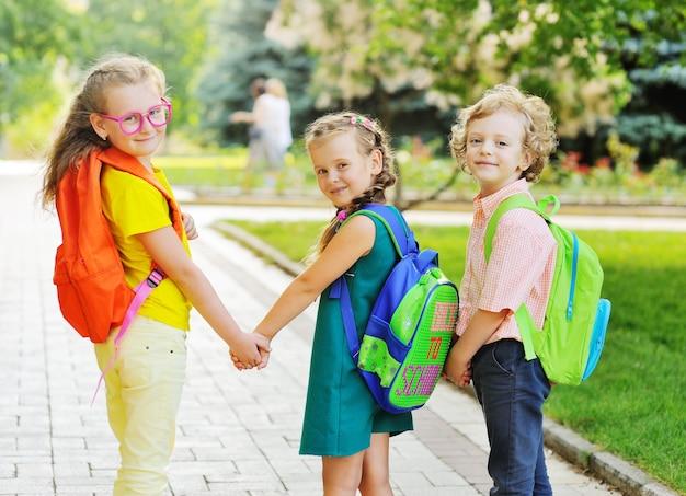 Трое школьников, две девочки и кудрявый мальчик с разноцветными школьными сумками, улыбаясь, держатся за руки и ...