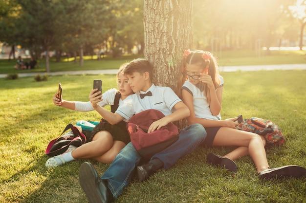 Трое школьных друзей сидят на траве под деревом и играют в гаджеты. друзья не общаются по жизни предпочитая телефон