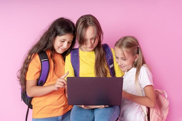 Три школьницы с энтузиазмом смотрят на ноутбук