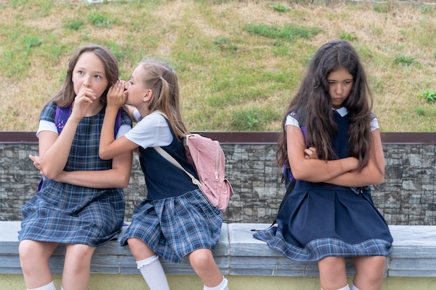 Three schoolgirls are sitting in the schoolyard