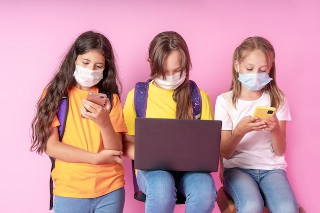 Три школьницы в медицинских масках держат смартфоны и ноутбук