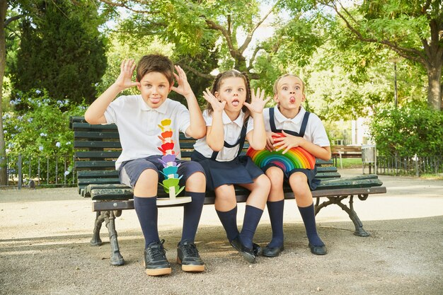 공원에서 벤치에 앉아 카메라에 얼굴을 만드는 세 학교 친구