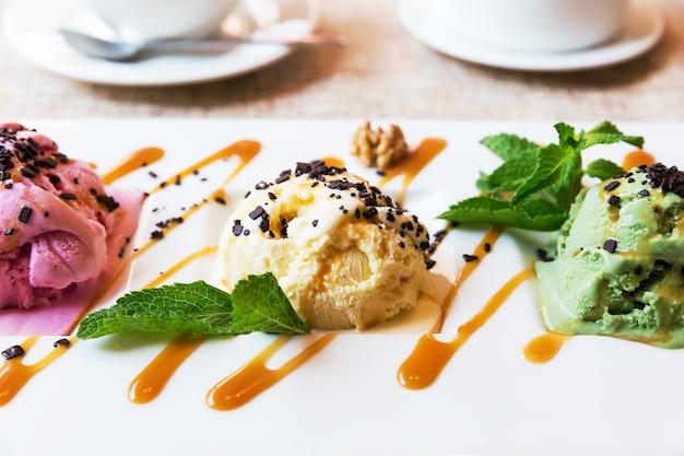 カフェのボウルにピスタチオ、ストロベリー、バニラアイスクリームの3つのスクープ
