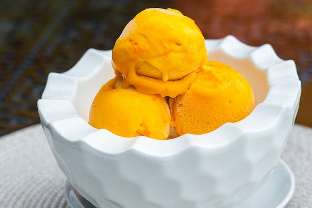 夏のカフェのテーブルの上の白いボウルに黄色いアイスクリームの3スクープ