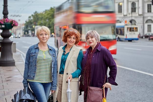 세 명의 수석 유럽 여성이 백그라운드에서 트래픽과 빨간색 이층 버스가있는 도심의 거리를 걸어갑니다.