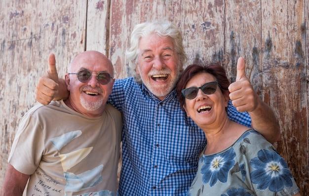 Трое пожилых людей вместе стоят перед старой деревянной дверью и смеются от счастья - активные пенсионеры и концепция развлечения