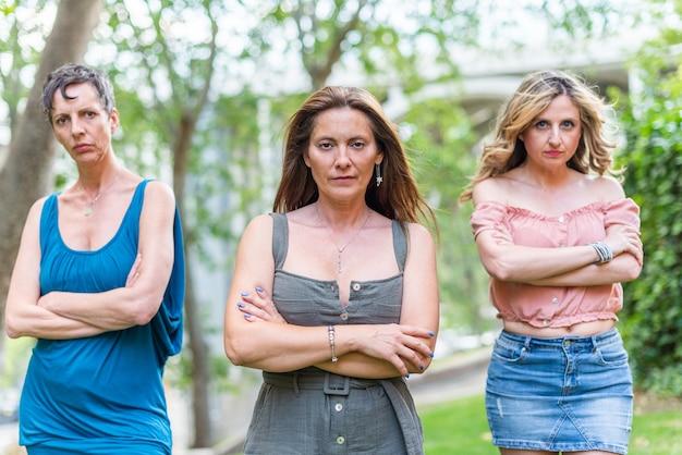 腕を組んでカメラに向かっている3人の真面目な成熟した女性の友人。一緒に時間を共有し、楽しんでいる中年の友人。
