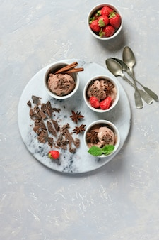 Three servings of chocolate ice cream with chocolate, mint and strawberry