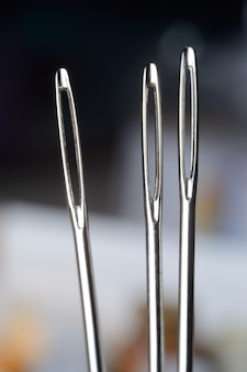 Three sewing needles on the background of many multi-colored babinets. needle eye. macro.
