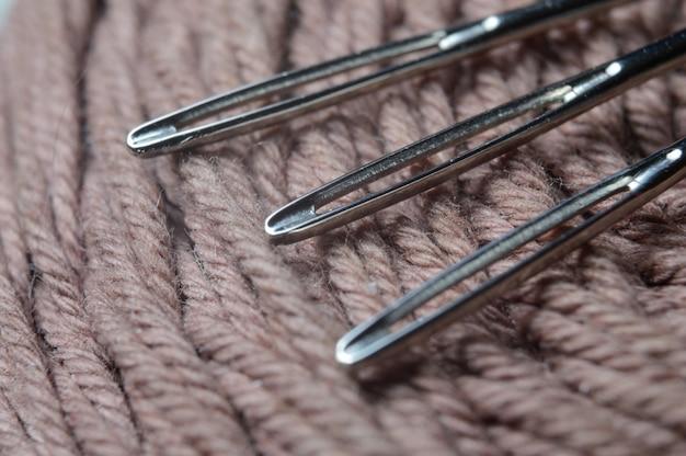3本のミシン針が糸の付いた茶色のボビンの上にあります。