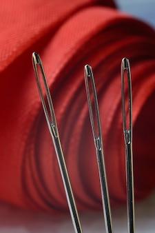 赤い布の背景に3本のミシン針。閉じる。