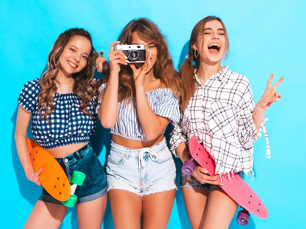 Three sexy beautiful stylish smiling girls with colorful penny skateboards. women in summer checkered shirt clothes posing. models taking pictures on retro photo camera