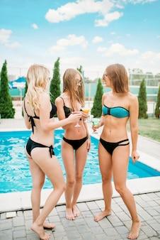 スイミングプールとサングラスの3人のセクシーな女の子がカクテルを飲みます。リゾートの休日。夏休みに日焼けした女性の楽しみ