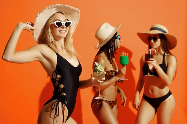 Three sexy women in swimsuits poses with coctails on orange