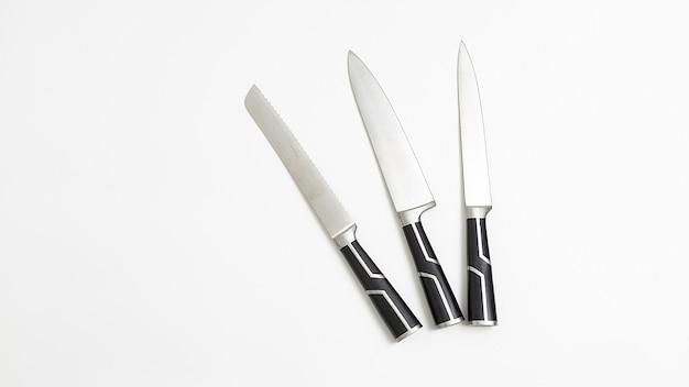 검은 손잡이가 달린 세 개의 날카로운 부엌 칼. 흰색 배경 flatlay. 평면도