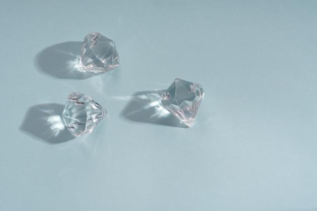 Три блестящих камня бриллиантов на синем фоне с копией пространства