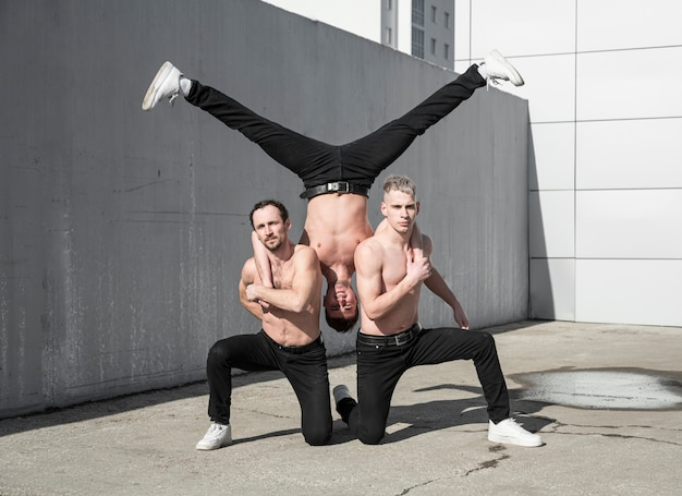 Три хип-хоп артиста без рубашки, практикующих позу