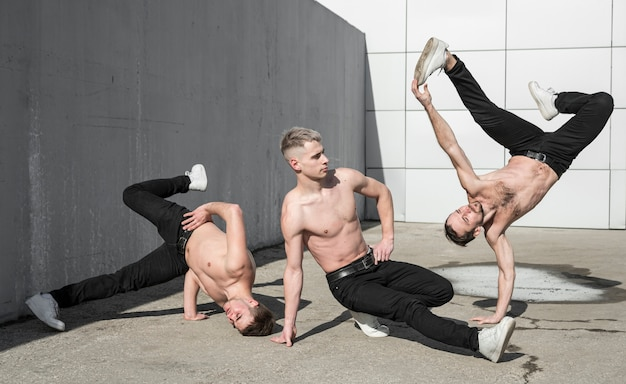 Three shirtless hip hop dancers outside