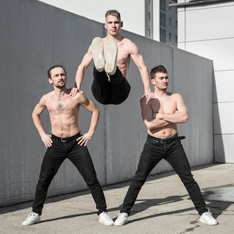 Three shirtless hip hop performers posing together outside