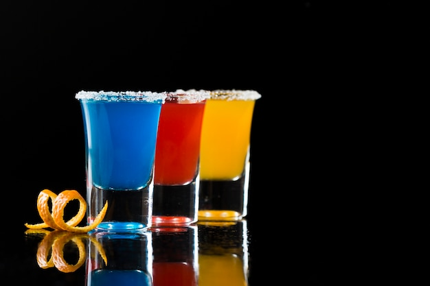 Three shot glasses with cocktails and coy space