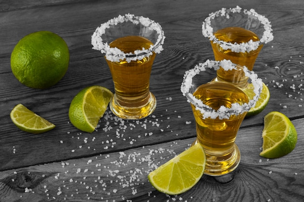 Three shots of gold tequila with lime and salt on the black background