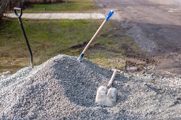 Three shovels and pile of gravel