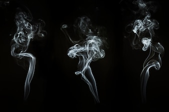 Three silhouettes of smoke floating