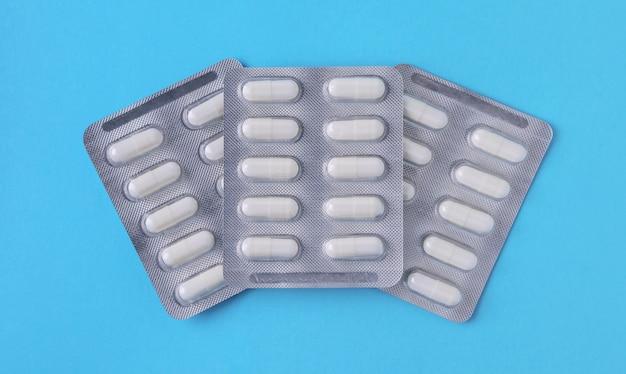 Три серебряные упаковки белых таблеток на синем фоне. вид сверху. концепция аптеки.