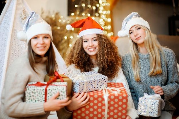 세 자매 아름다운 젊은 여성이 장식 된 가족 집에서 크리스마스를 축하
