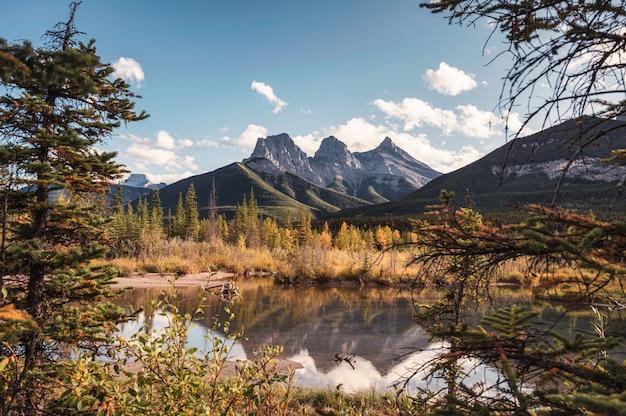 カナダ、キャンモアの池の秋の森の反射で3人の姉妹山