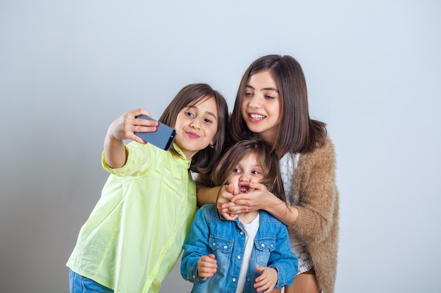 Three sisters posing and taking selfies