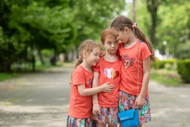公園の真ん中に立っている3人の姉妹が耳元で抱き合って何かを言っている
