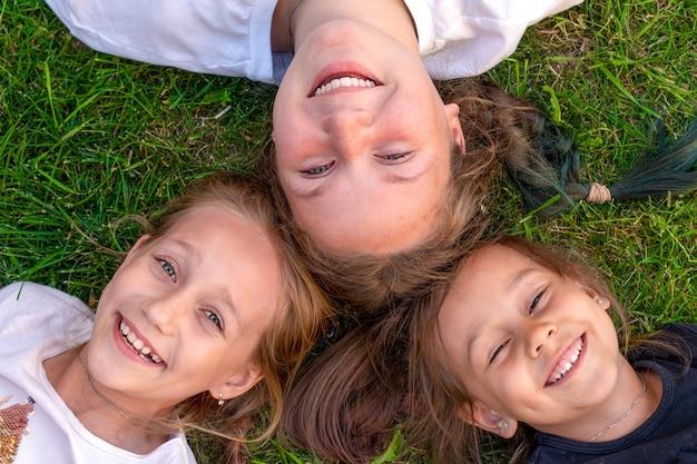 세 자매 여름 초상화입니다. 귀여운 소녀들이 풀밭에 누워 웃고 있습니다. 웃는 어린이 야외. 여름의 개념입니다.