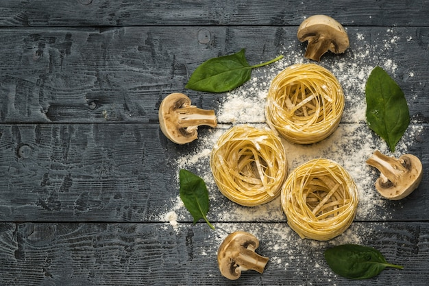 Три мотка макарон, три половинки грибов и листья шпината на деревянном столе. место для текста.