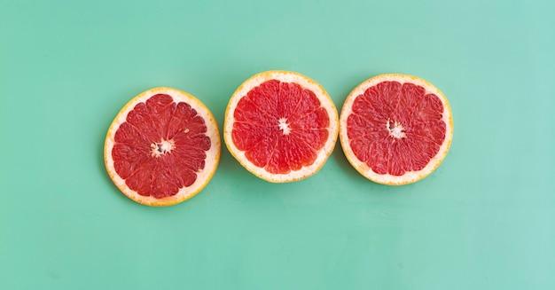 緑の背景に赤脾髄を置いた3つのスライスしたグレープフルーツ