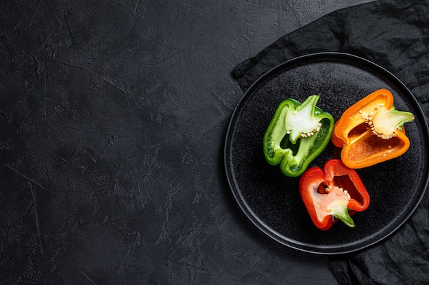 Three sliced orange, green and red bell peppers. black wall. top view. space for text