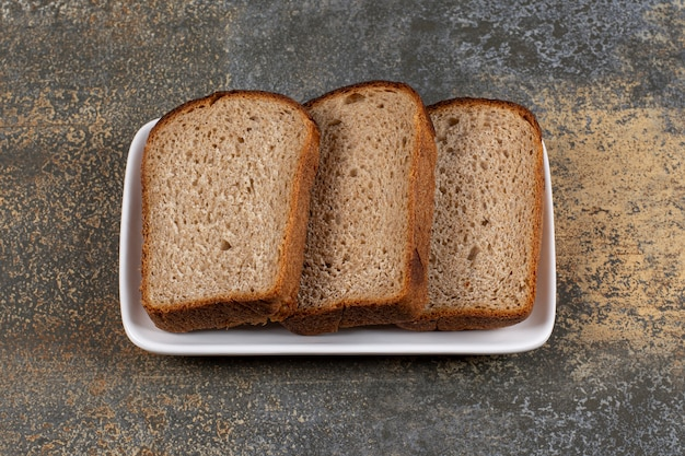 Three slices of black bread on white square plate