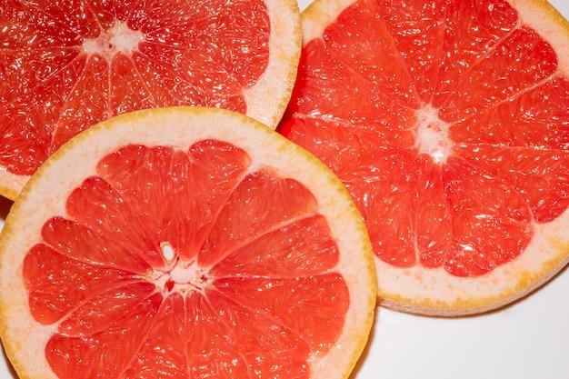 Три ломтика грейпфрута, изолированные на белом фоне. круглый ломтик свежих фруктов.