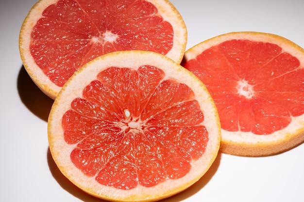 흰색 표면에 절연 자 몽의 세 조각. 신선한 과일의 둥근 조각.