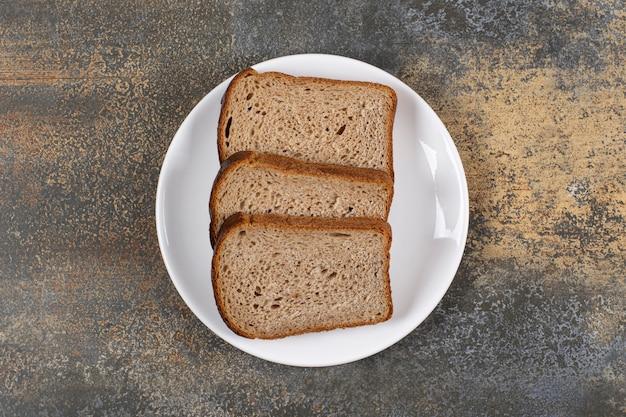 하얀 접시에 검은 빵 세 조각입니다.