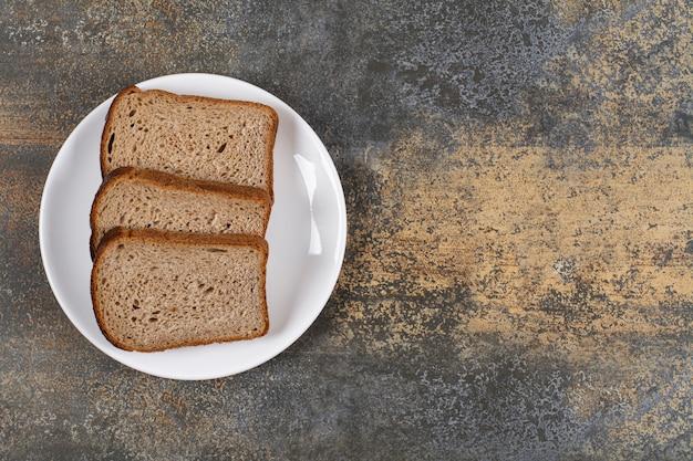 白い皿に黒いパンの3つのスライス。