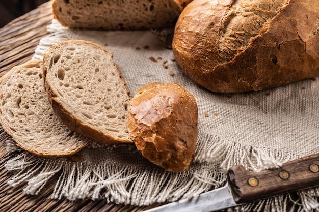 소박한 천과 측면에 칼이 있는 나무 배경에 신선한 피각질의 빵 세 조각.