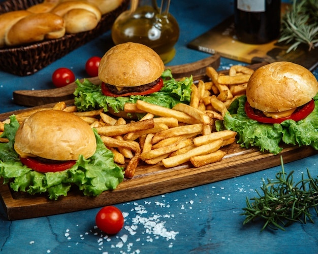 Three small beef burgers and french fries served on wooden board